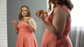 Deprimerad överviktig kvinnlig som framme äter donuts av spegeln och att äta oordning arkivbilder