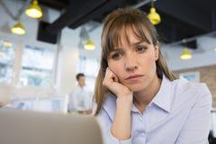 Deprimerad affärskvinna i regeringsställning bak hennes lapto Fotografering för Bildbyråer