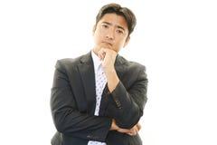 Deprimerad asiatisk affärsman. arkivbild
