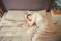 Deprimerad asiatisk man som klandrar på telefonen på säng royaltyfri fotografi