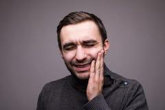 Deprimerad dåligt man som har tandvärk och den rörande kinden som isoleras på mörk bakgrund arkivbild