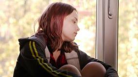 Deprimerad flicka hemma flicka nära SAD fönster arkivfilmer