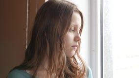 Deprimerad flicka hemma flicka nära SAD fönster 4k UHD arkivfilmer