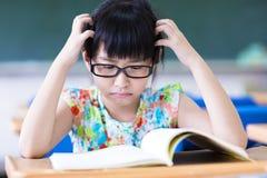 Deprimerad flicka som studerar i klassrumet Royaltyfri Foto