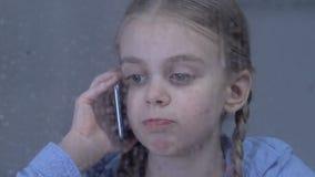 Deprimerad flicka som talar på telefonlidandeensamhet, missande upptagna föräldrar arkivfilmer