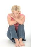 Deprimerad fundersam olycklig ung kvinna som bara sitter på golvet som ser bedrövligt Arkivbild