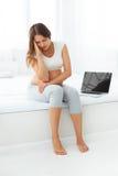 Deprimerad gravid kvinna med en bärbar datordator, medan sitta på arkivfoto