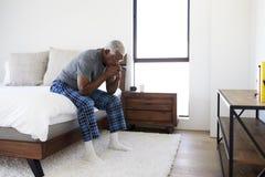 Deprimerad hög man som hemma ser olyckligt sammanträde på sida av säng med huvudet i händer fotografering för bildbyråer