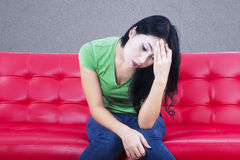 Deprimerad kvinna för närbild på den röda soffan Royaltyfri Foto