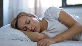 Deprimerad kvinna propped upp på kudden i säng stock video