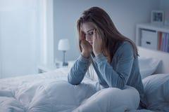 Deprimerad kvinna som är vaken i natten fotografering för bildbyråer