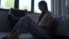 Deprimerad kvinna som använder den smarta telefonen i hennes sovrum arkivfilmer