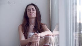 Deprimerad kvinna som gråter vid fönstret lager videofilmer