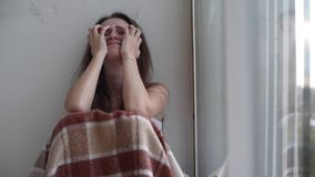 Deprimerad kvinna som gråter vid fönstret arkivfilmer