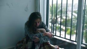 Deprimerad kvinna som gråter vid fönstret med regn stock video