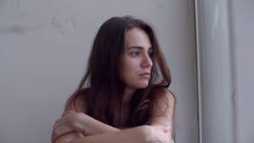 Deprimerad kvinna som ut ser fönstret lager videofilmer