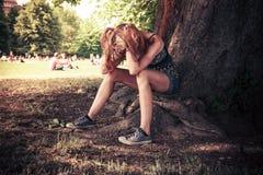 Deprimerad kvinnasittng under ett träd Royaltyfri Foto