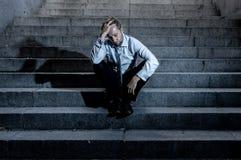 Deprimerad ledsen affärsman i sammanlagd förtvivlan som avverkar hopplöst och frustrerat sammanträde i stadstrappa royaltyfri foto