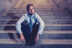 Deprimerad ledsen affärsman i sammanlagd förtvivlan som avverkar hopplöst och frustrerat sammanträde i stadstrappa arkivfoton