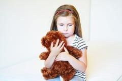 Deprimerad liten flicka som kramar nallebjörnen Royaltyfria Bilder