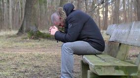 Deprimerad man i parkera på bänk