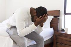 Deprimerad man som hemma ser olyckligt sammanträde på sida av säng med huvudet i händer royaltyfri bild