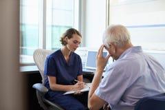 Deprimerad manlig patient för doktor In Consultation With Royaltyfri Foto