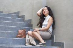 Deprimerad och desperat asiatisk kinesisk affärskvinna som gråter bara att sitta på spänning och fördjupning för gatatrappuppgång arkivfoton