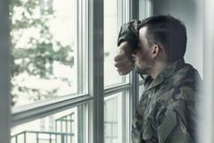 Deprimerad och ledsen soldat i grön likformig med trauma efter kriganseende nära fönstret arkivbilder