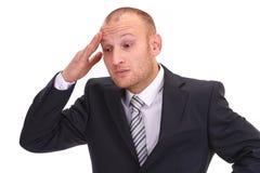 Deprimerad orakad affärsman som in lyfter hans hand på hans huvud Royaltyfri Fotografi