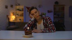 Deprimerad tonåring som firar födelsedagen som ser kakan med stearinljuset, icke-favorit stock video