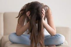Deprimerad tonåring som har problem, hållande huvud för stressad kvinna royaltyfri foto