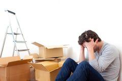 Deprimerad ung man medan hans rörande ut hans lägenhet Royaltyfri Fotografi