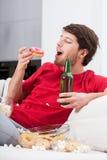 Deprimerad ung man som äter sötsaker arkivbilder