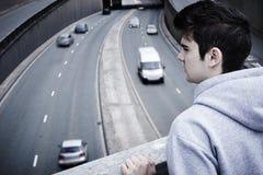 Deprimerad ung man som beskådar självmord på vägbron Arkivfoto