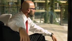 Deprimerad vuxen affärsman med ett huvudvärksammanträde i lobbyen och att se i fönstret lager videofilmer