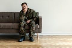 Deprimerad yrkesmässig soldat i grönt enhetligt sammanträde bara hemma Kopieringsutrymme på väggen royaltyfria foton