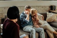 Deprimerade krama mitt-ålder par som sitter på en soffa och gråta arkivfoto