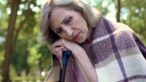 Deprimerat åldrigt kvinnasammanträde på bänk i trädgård med att gå pinnen, ensamhet arkivfoton