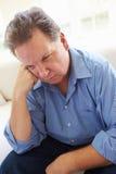 Deprimerat överviktigt mansammanträde på soffan royaltyfri bild