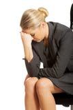 Deprimerat affärskvinnasammanträde på fåtöljen Arkivbilder