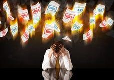 Deprimerat affärsmansammanträde under bränningskatt- och räkninglegitimationshandlingar royaltyfri foto