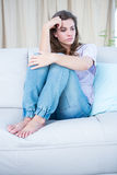 Deprimerat brunettsammanträde på hennes soffa Royaltyfri Foto