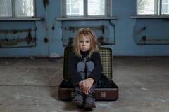Deprimerat flickasammanträde i resväska royaltyfria foton