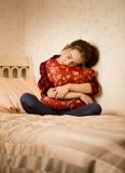 Deprimerat flickasammanträde på säng och omfamnakudde Royaltyfri Foto