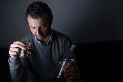 Deprimerat missbruka för man av alkohol Royaltyfri Fotografi