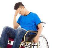 Deprimerat och handikappat mansammanträde på en rullstol Arkivfoto