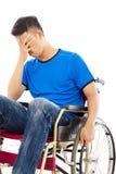 Deprimerat och handikappat mansammanträde på en rullstol Royaltyfria Bilder