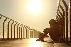Deprimerat sammanträde för ledsen tonåringflicka i en bro på solnedgången Arkivbild