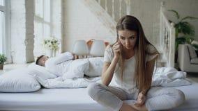 Deprimerat sammanträde för ung kvinna i säng och gråt medan hennes boylfriend som hemma ligger i säng lager videofilmer